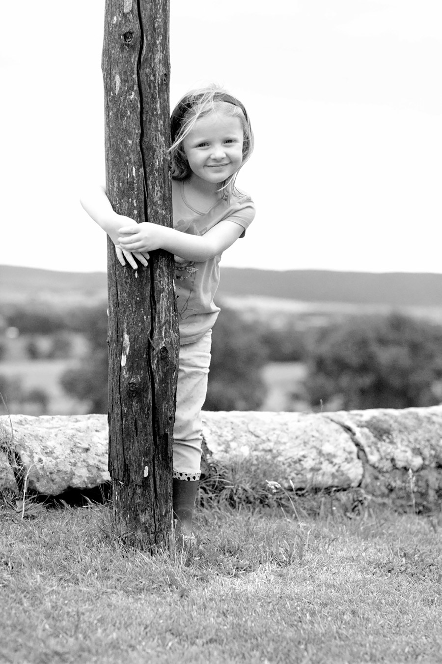 Girl with arms wrapped around a post